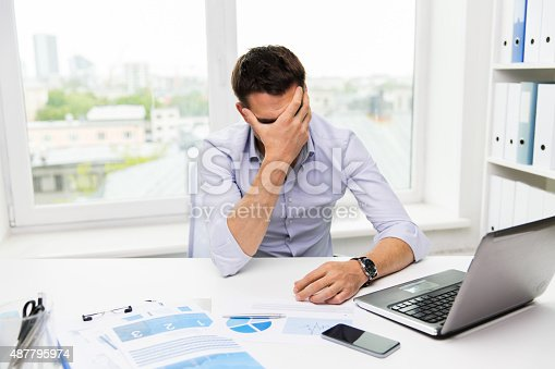 istock businessman with laptop and papers in office 487795974