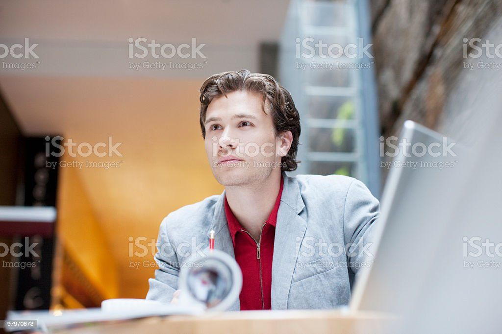 Businessman with laptop at table looking pensive royalty-free stock photo