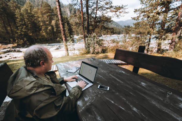 Businessman with laptop being on leave Adult man entrepreneur is sitting outdoors at the table of a mountain tourist resort during his vacations and working remotely via wi-fi with his business project using the laptop and gadgets around park ranger stock pictures, royalty-free photos & images