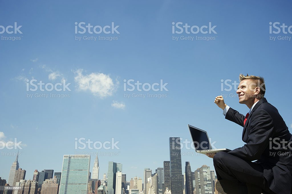 Businessman with Laptop Celebrating Outdoors at City Skyline royalty-free stock photo