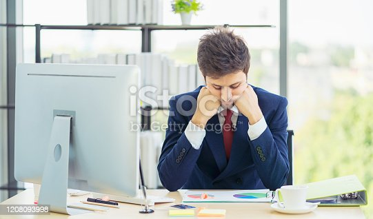 833210686 istock photo Businessman with laptop computer and papers working in office. Man having a headache. Tired and worried businessman at workplace in office. Stress and depression. 1208093998