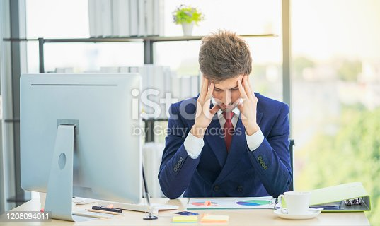 833210686 istock photo Businessman with laptop computer and papers working in office. Man having a headache. Tired and worried businessman at workplace in office. Stress and depression. 1208094011