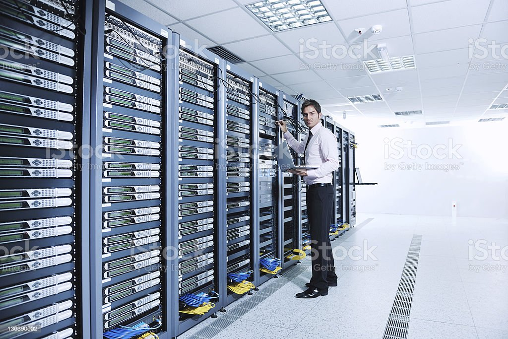 businessman with laptop in network server room stock photo