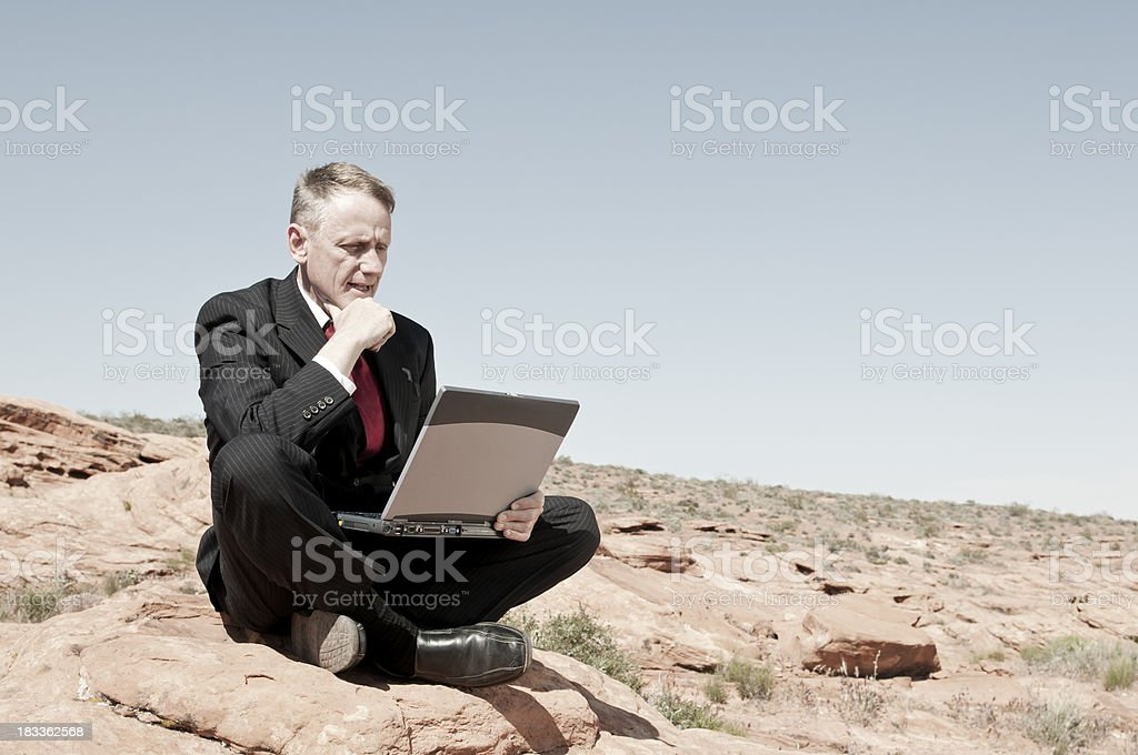 Businessman with laptop in the harsh environment - VI stock photo