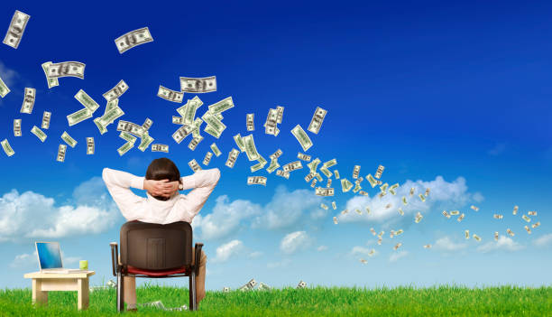 businessman with laptop watching view with flying large group of money stock photo