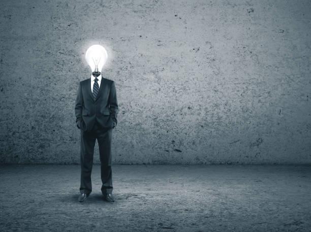 Businessman with lightbulb instead of a head stock photo