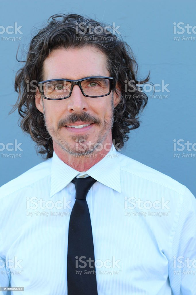 Businessman with long hair wearing glasses stock photo