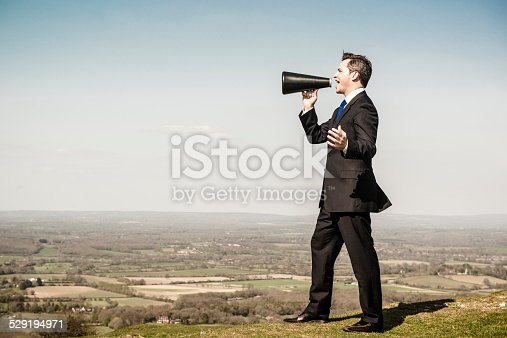 Businessman speaking through a megaphone announcing from a hill. Communication concept.