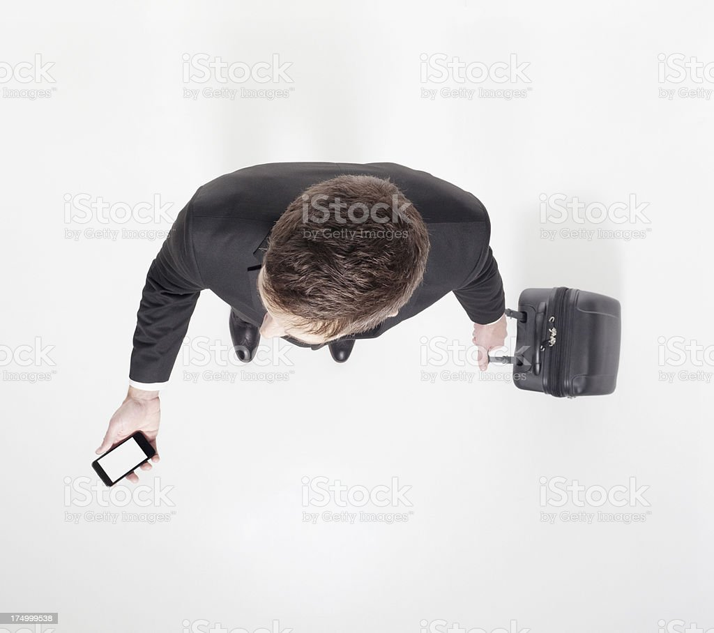 Businessman with luggage and smartphone royalty-free stock photo