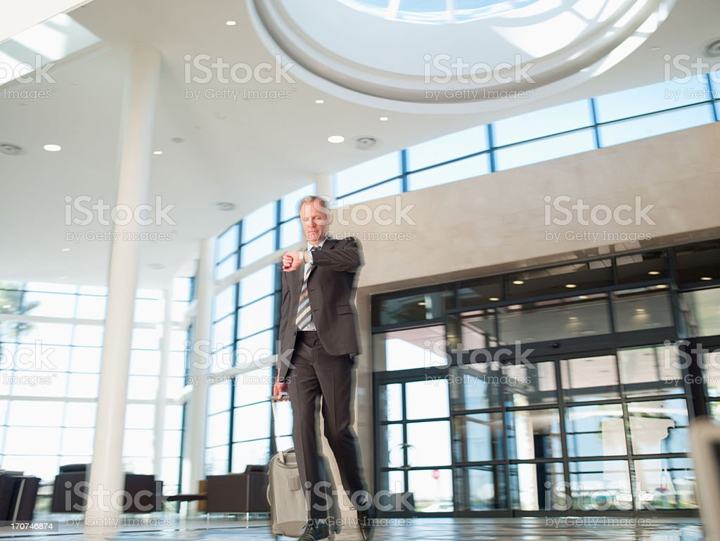 Businessman with luggage checking wristwatch royalty-free stock photo