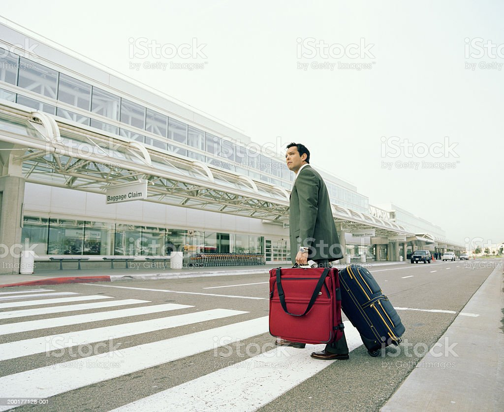 Businessman with luggages crossing road to airport  35-39 Years Stock Photo