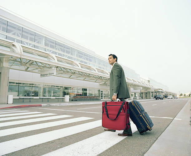 Businessman with luggages crossing road to airport stock photo