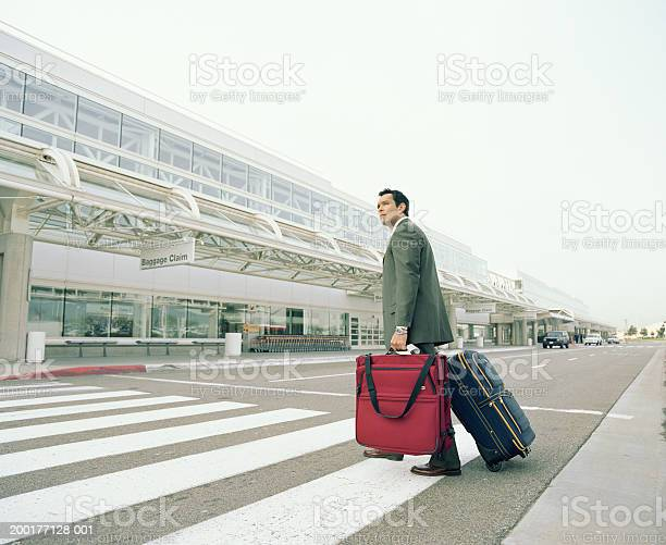 Businessman With Luggages Crossing Road To Airport Stock Photo - Download Image Now