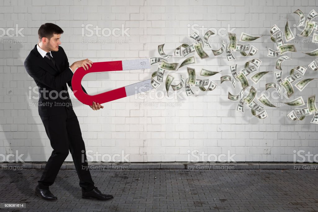 Businessman With Magnet Attracting Banknotes stock photo