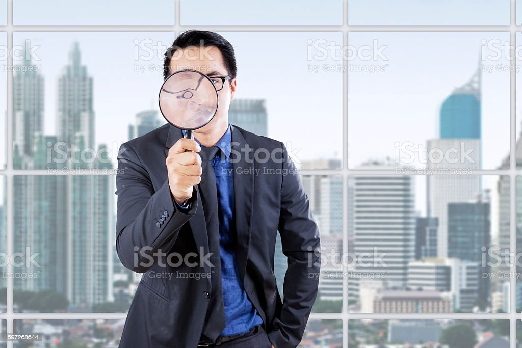 Businessman with magnifying glass in office Lizenzfreies stock-foto