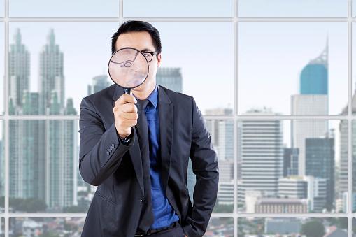 Businessman With Magnifying Glass In Office Stockfoto und mehr Bilder von Asiatischer und Indischer Abstammung