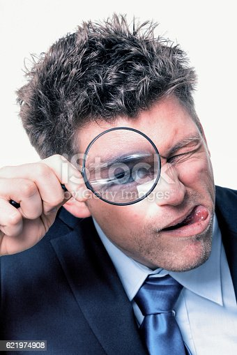 istock businessman with magnifying glass 621974908