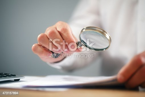istock Businessman with magnifying glass reading documents 473157894