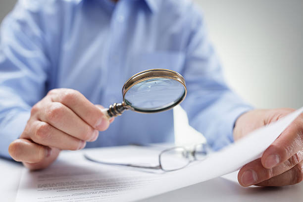 Businessman with magnifying glass reading documents Businessman reading documents with magnifying glass concept for analyzing a finance agreement or legal contract scrutiny stock pictures, royalty-free photos & images
