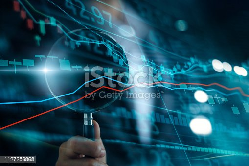 istock Businessman with magnifying glass search of investing and stock market. Gain and profits with candlestick charts. Stock Market Analysis. Finance data concept. 1127256868