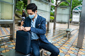 Businessman with mask for air pollution sitting on bus station and packing his bag