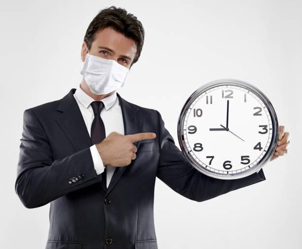 時計を示すマスクを持つビジネスマン - 出勤 ストックフォトと画像