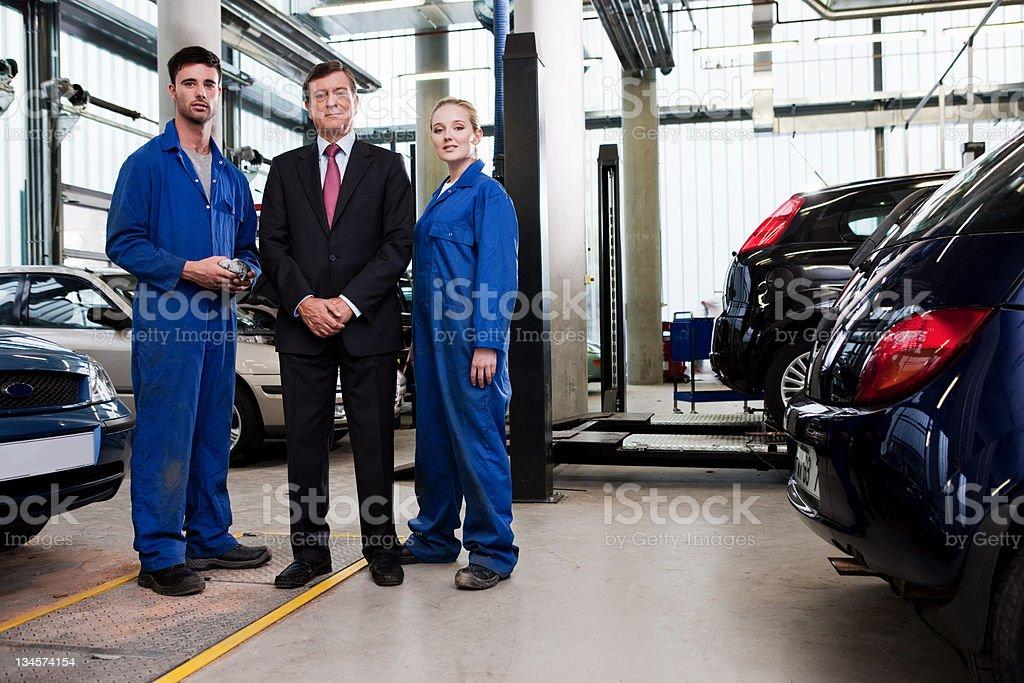 Businessman with mechanics in repair garage stock photo