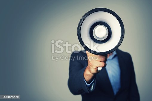 istock businessman with megaphone in hand in front of face 996828576
