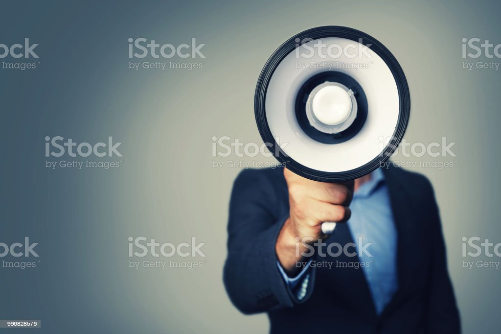 businessman with megaphone in hand in front of face stock photo