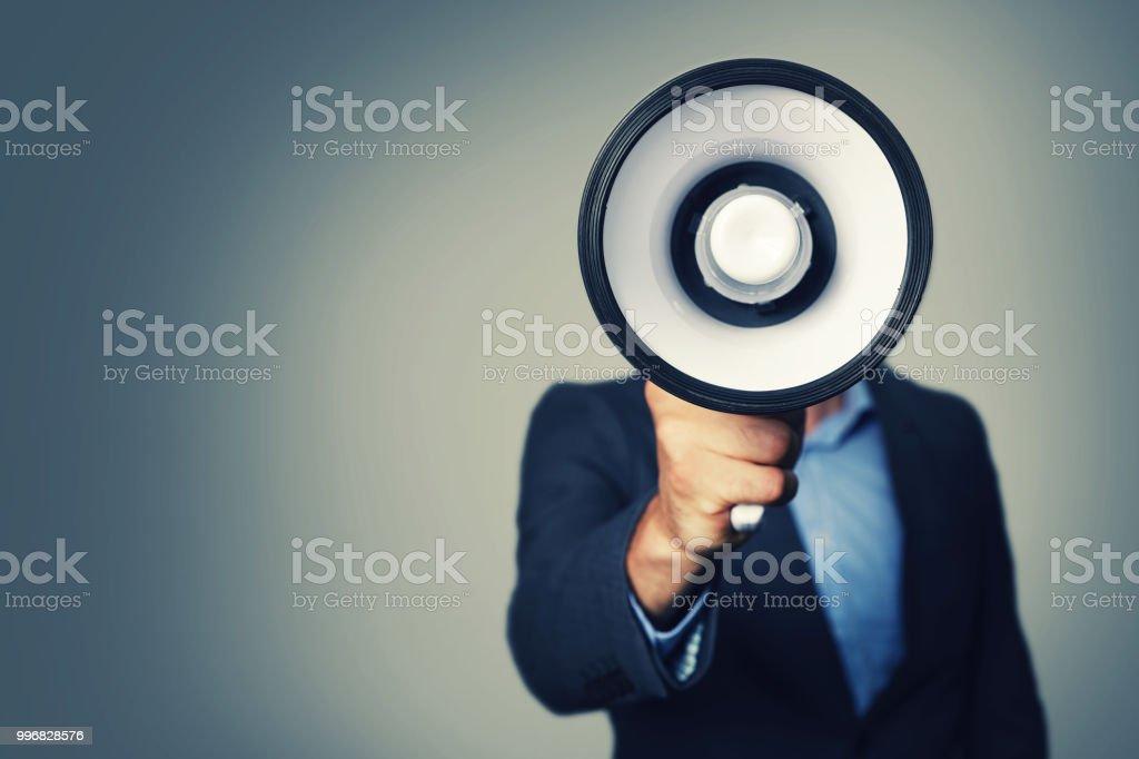 Geschäftsmann mit Megaphon in der Hand vor Gesicht – Foto
