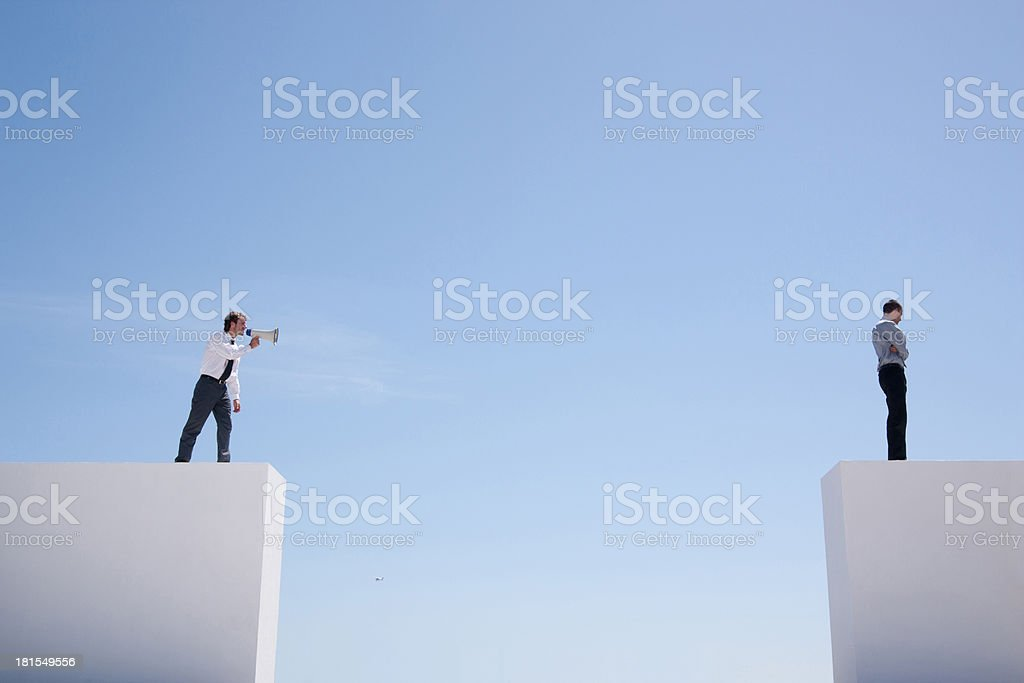 Businessman with megaphone on wall shouting at businessman on wall with gap stock photo