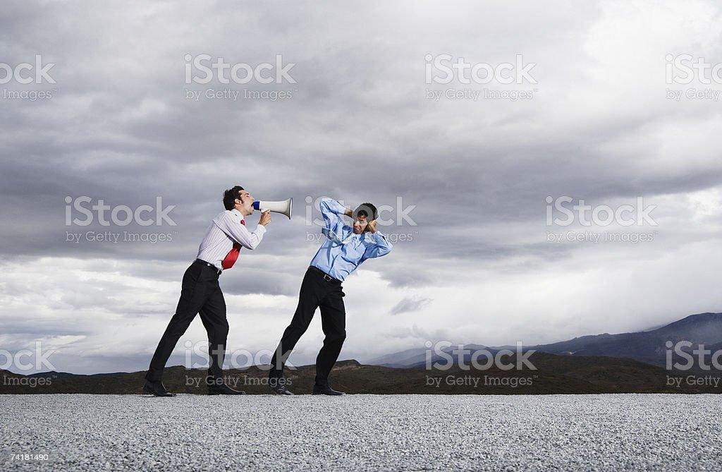 Empresário com Megafone ao ar livre gritar no homem foto de stock royalty-free