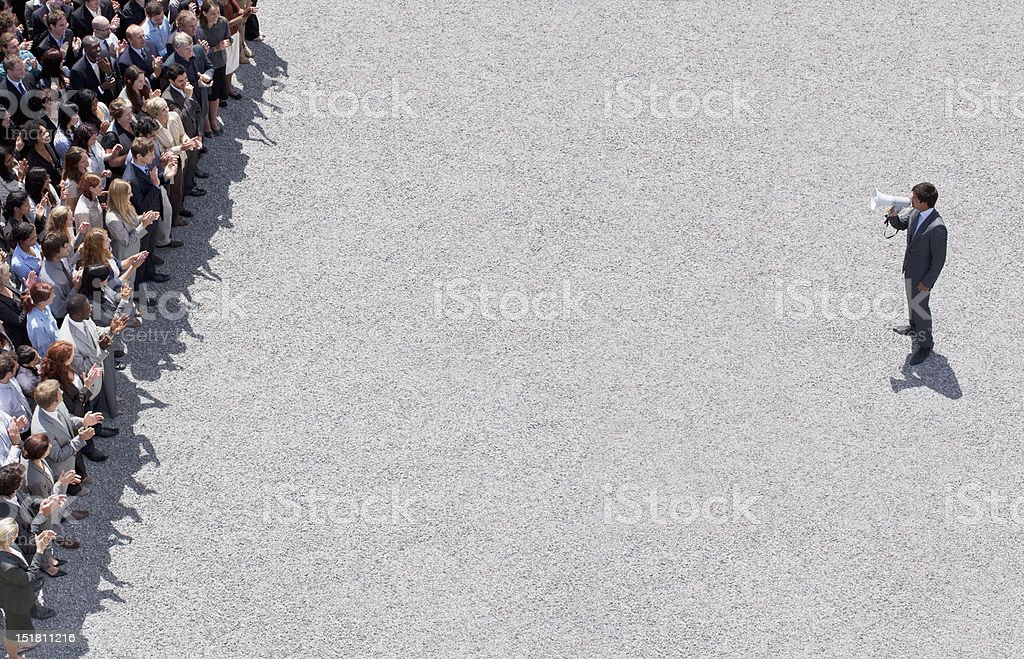 Businessman with megaphone talking to crowd of people stock photo