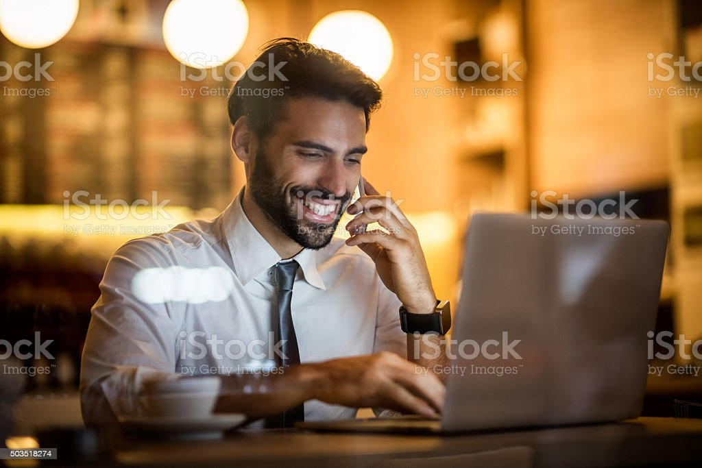 Businessman with mobile phone and laptop inside coffee shop stock photo
