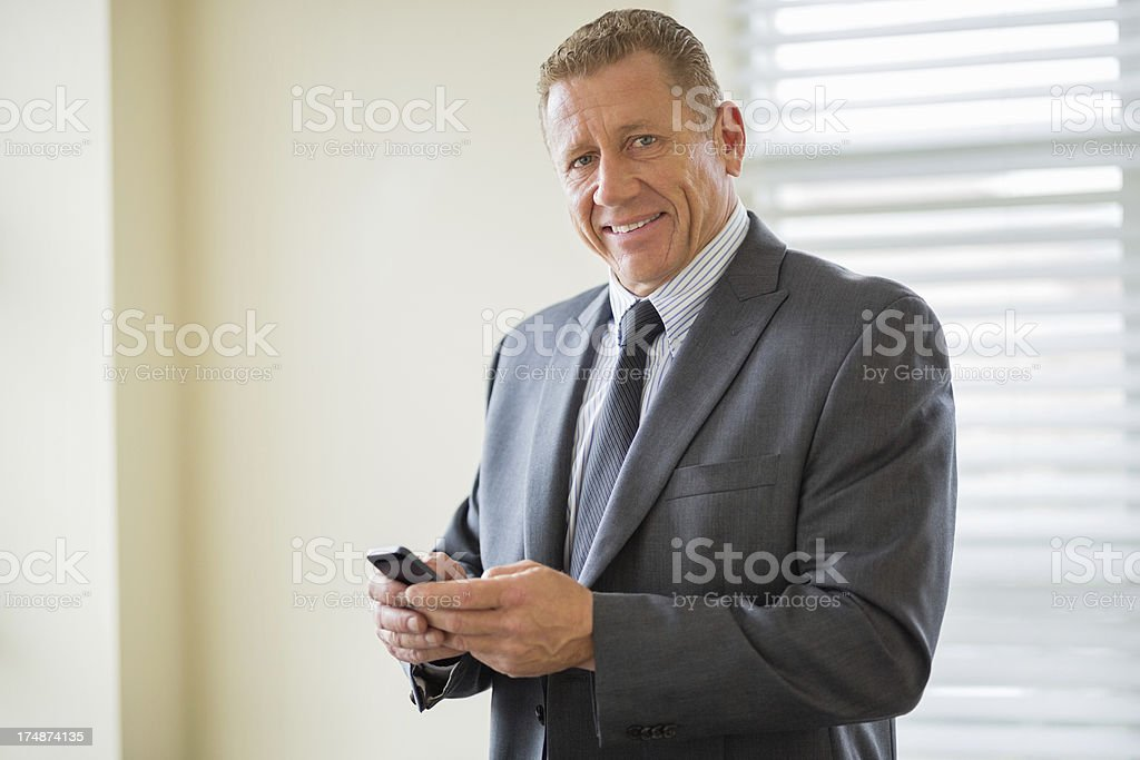 Businessman With Mobile Phone In Office royalty-free stock photo