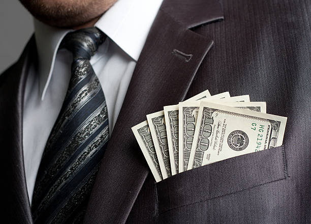 Businessman with money in suit pocket stock photo