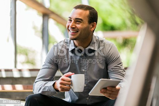istock Businessman with mug and digital tablet on steps 541585672