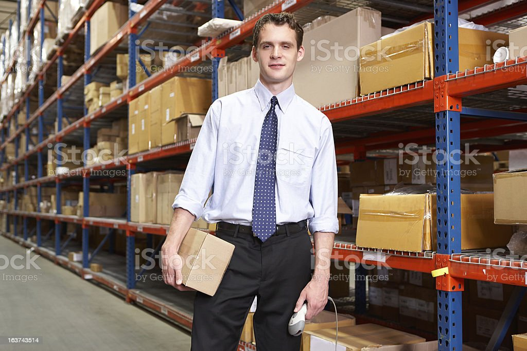 Businessman With Package And Scanner In Warehouse royalty-free stock photo