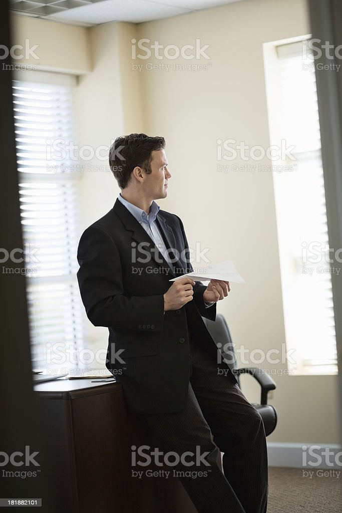 Businessman With Paper Airplane Looking Away royalty-free stock photo