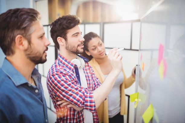 Homem de negócios com parceiros, olhando o quadro no escritório criativo - foto de acervo