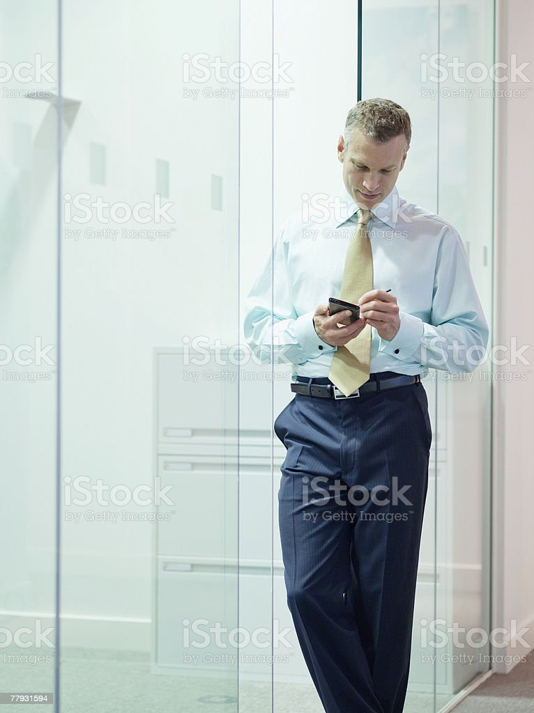Businessman with PDA in office hallway royalty-free stock photo
