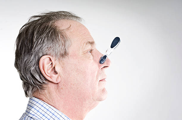 Businessman With Peg On His Nose. stock photo