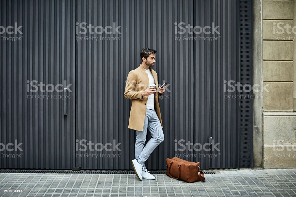 Businessman with phone and cup looking away Full length of businessman holding disposable cup and mobile phone. Executive is looking away while standing by bag. He is on sidewalk against building in city. 35-39 Years Stock Photo