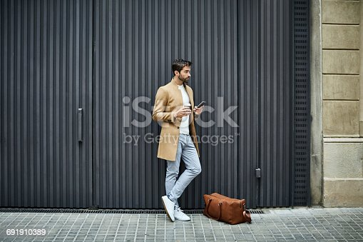 Full length of businessman holding disposable cup and mobile phone. Executive is looking away while standing by bag. He is on sidewalk against building in city.