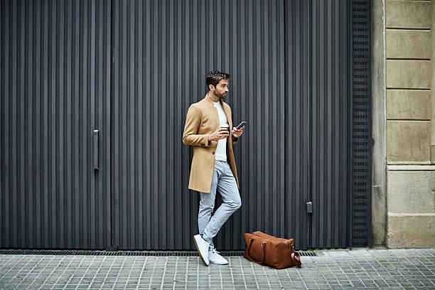 businessman with phone and cup looking away - handytasche stock-fotos und bilder
