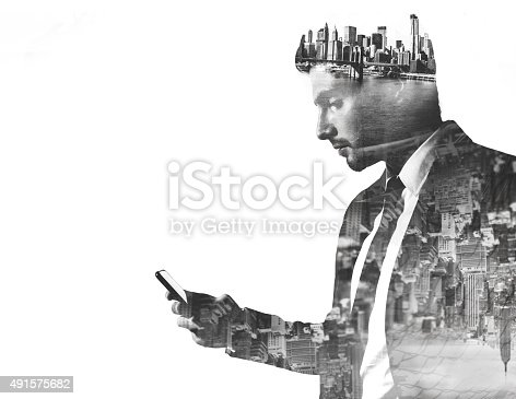 istock Businessman with phone double exposed with city images 491575682