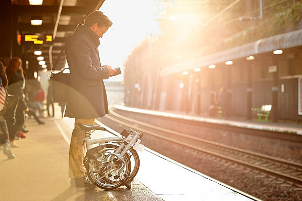 Businessman with phone on train platform Businessmen waiting on train platform using mobile phone foldable stock pictures, royalty-free photos & images