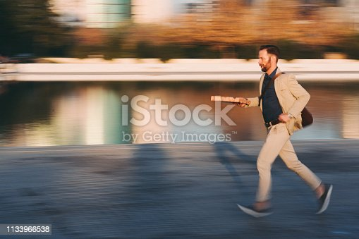 Young man holding pizza box is running to work