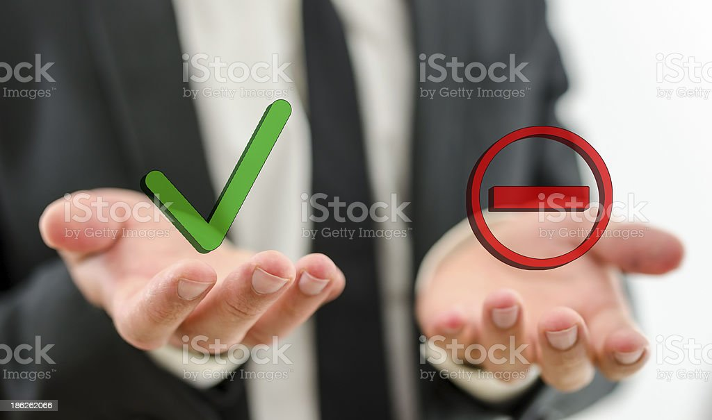 Businessman with positive and negative symbols in hand stock photo