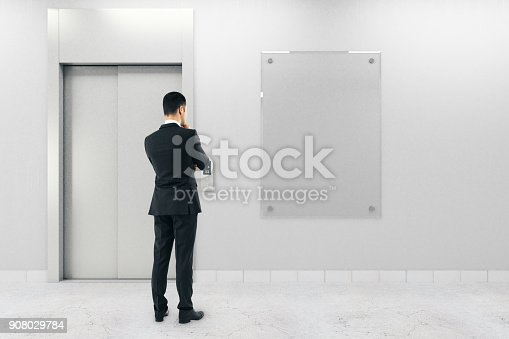 638591126istockphoto Businessman with poster and elevator 908029784
